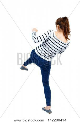 back view of woman funny fights waving his arms and legs. Rear view people collection. backside view of person.  Isolated over white background. Girl in a striped sweater's back and hits his foot.