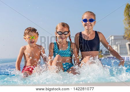 happy children playing on the swimming pool at the day time. Concept of friendly family.