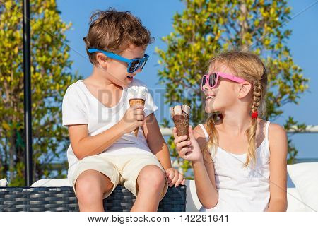 Two happy children eating ice cream near swimming pool at the day time. Concept healthy food.