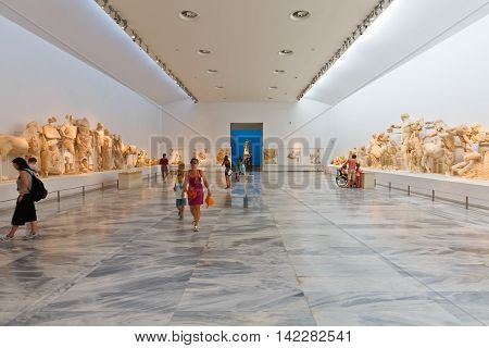 OLYMPIA, GREECE - AUGUST 08, 2016: People in the main room of the Archaeological museum in Olympia with statues from the temple of Zeus on August 08, 2016.