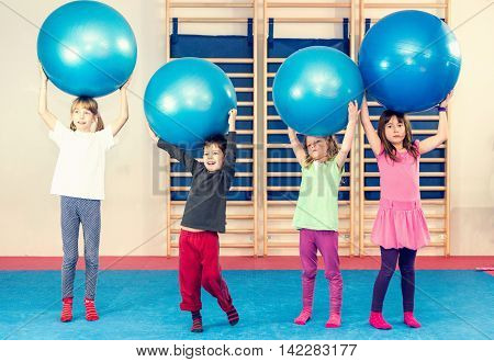 Children at physical education class playing with fitness balls