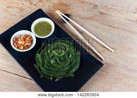 sea grapes or green caviar and spicy sauce on a black dish the wood table