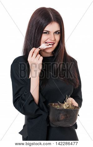 Wicked young witch with a potion in a cauldron isolated on white background