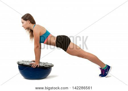 Young sports girl does exercises push-ups on spotrivnom simulator bosu. Portrait in full growth. View profile.