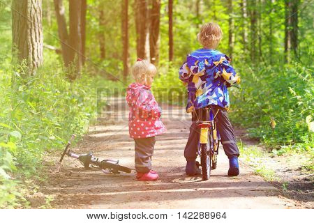 kids sport - little boy and girl riding bikes in summer forest