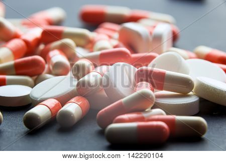 Pharmacy theme cure in container for health. Heap of red orange white round capsule pills with medicine antibiotic in packages. Drug prescription for treatment medication. Pharmaceutical medicament.