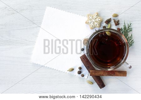 festive background with black tea decorated with fragrant spices and ginger cookies in the form of a Christmas Star top view / Christmas fragrant tea