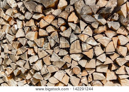 Woodpile texture of birch wood. Background of rustic style. Chopped cordwood stacked and ready for winter.