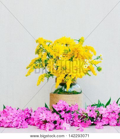 a bouquet of flowers chrysanthemums goldenrod and daisies in a vase among the Phlox on a gray background. tinted photo