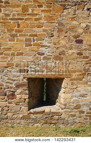 Fragment of ancient fortress wall with embrasure. Architecture exterior background