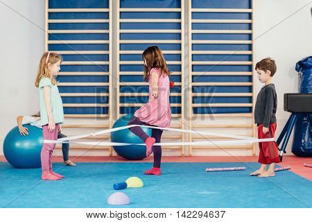 Little children playing with elastic band on physical education class
