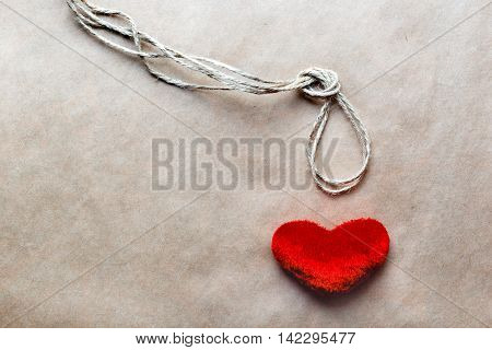 concept hangman knot with plush red heart on kraft paper background