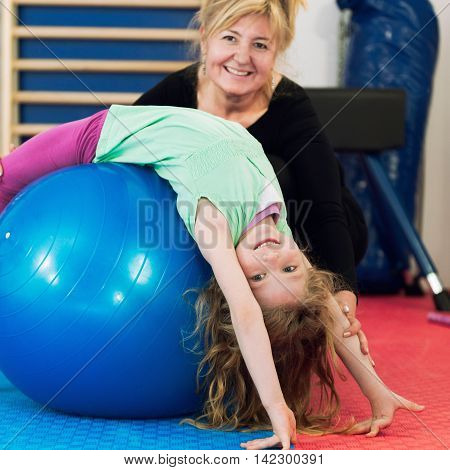 Physical therapist working with little girl in school gymnasium exercising with fitness ball