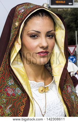 QUARTU S.E., ITALY - September 21, 2014: Parade of Sardinian costumes and floats for the grape festival in honor of the celebration of St. Helena - portrait of a beautiful girl in traditional Sardinian costume - Sardinia
