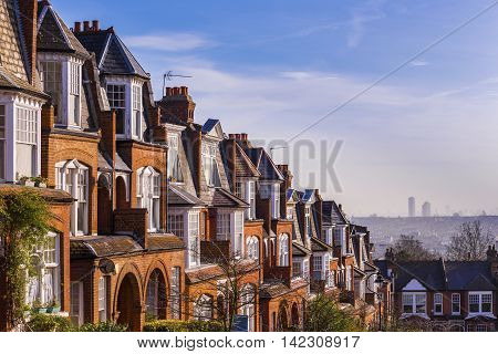 Typical British orange brick houses and skyline of east London on a sunny winter morning - London, UK
