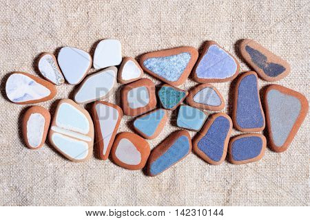 pieces of colorful tiles polished by the sea closeup on textile background