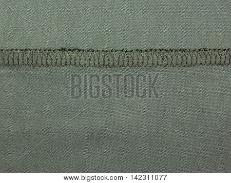 texture of green fabric sewn into her seams , khaki close-up