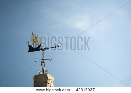 Vane of an Antique ship ovel a cloudy sky