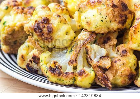 tasty appetizer roasted cauliflower in white plate on wooden background