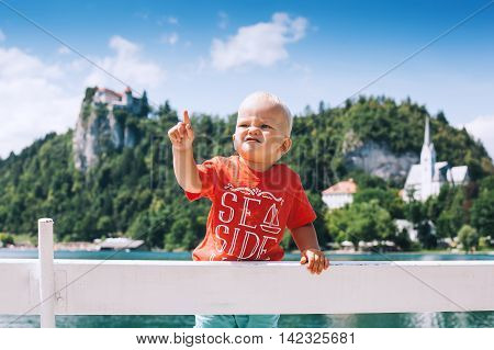 Adorable Child Boy At Summertime On The Lake Bled And Bled Castle Background