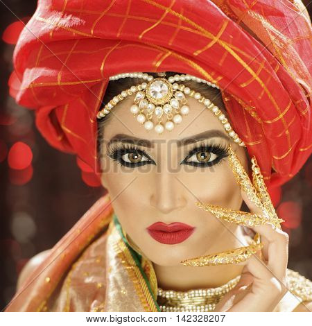 Portrait of a beautiful model in an ethnic Indian/Pakistani traditional outfit with heavy makeup and jewellery poster