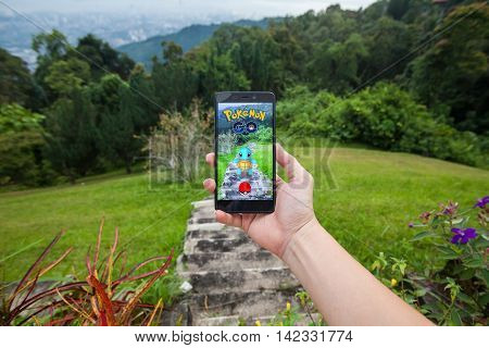 California, United States - July 23, 2016: Close up of a man holding a smartphone while playing Pokemon Go game and try to catch a Pokemon.