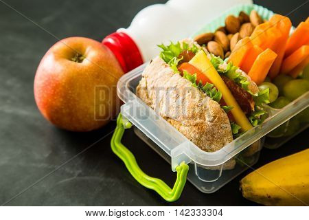 School lunch box with books and pencils in front of black board, copy space