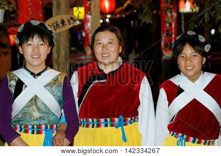 Lijiang China - April 18 2006: Three Chinese women wearing traditional Naxi clothing at a South Gate Square Restaurant