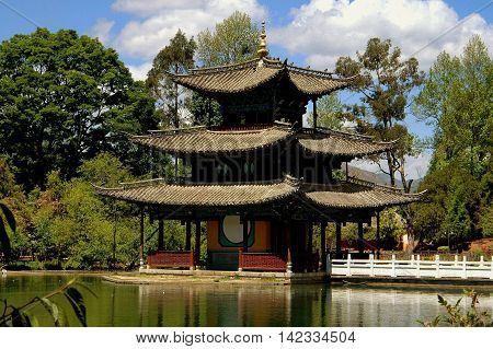 Lijiang China - April 19 2006: Elegant water pavilion with tiled flying eave roofs at Black Dragon Pool Park