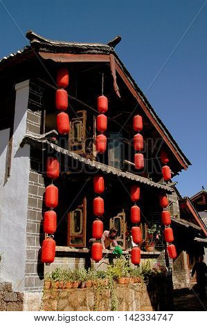 Lijiang China - April 19 2006: Strings of bright red Chinese lanterns hang from a traditional Naxi home
