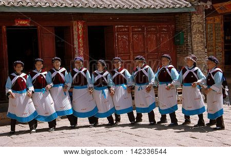 Shu He / Yunnan Province China - April 20 2006: A troupe of elderly Naxi women in traditional clothing perform native dances in the courtyard of a village home