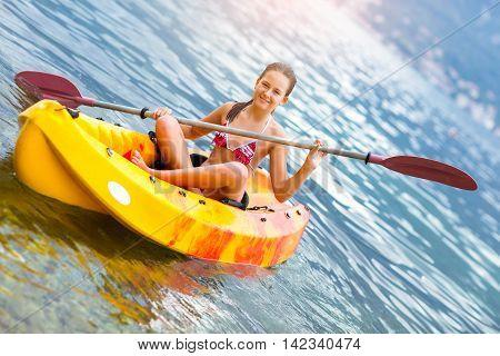 Girl enjoying paddling in kayak on the sea water during summer vacation