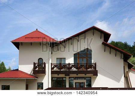 Cottage with red metal tile roof photo