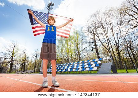 Full-length portrait of happy smiling teenage boy in sportswear, waving American flag, standing on the track