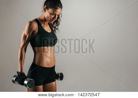Athletic Woman Resting With Weights At Her Sides