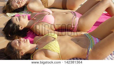 Three happy young female friends sunbathing