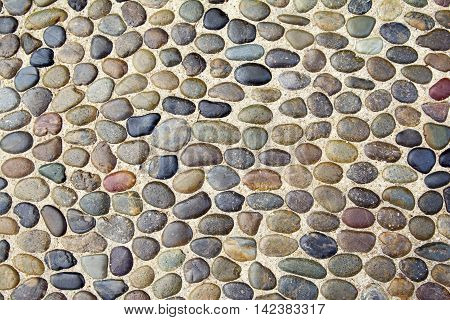 Pebble background texture with many pebbles of different sizes and shapes