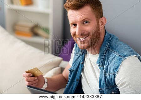 In a good mood. Delighted smiling handsome man sitting on the couch and using tablet while holding credit card