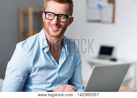 Rise your mood. Joyful content handsome man holding laptop and looking aside while leaning on the table