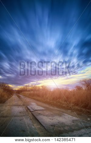 Long exposure work during sunsrise. Motion of clouds. plates of the road