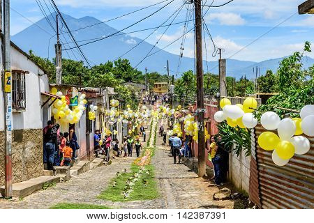 San Juan del Obispo Guatemala - June 24 2016: St John's Day procession approaches in village named after the patron saint. Acatenango Volcano behind. Near Antigua Guatemala's most famous Spanish colonial town & UNESCO World Heritage Site.