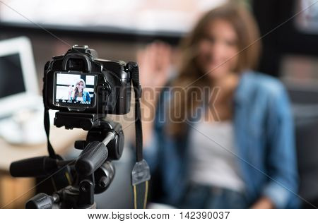 My favorite occupation. Close up of photo camera while positive delighted woman sitting in the background and posing in front of it while shooting a video