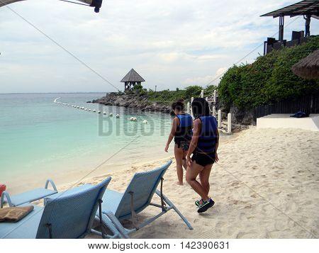 LAPU LAPU, CEBU / PHILIPPINES - JULY 28, 2011: Two women walk towards the ocean at the beach of Shangri-La's Mactan Resort and Spa.