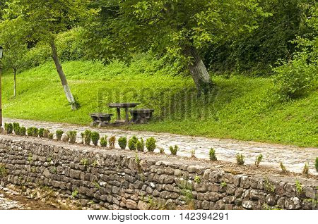 Alley with wooden benches along stone riverbed