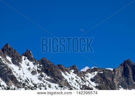 Half Moon over rocky mouintain peaks. North Cascades National Park Washington Pass WA USA.