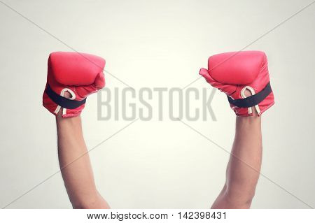 Two hands raised in the air wearing red hot boxing gloves