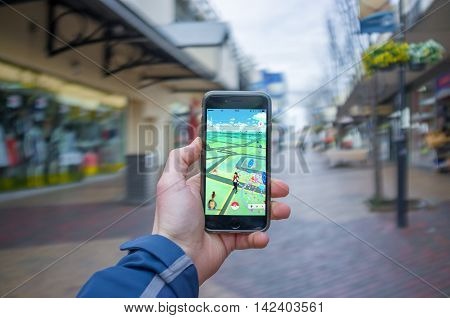 Male Hand Holding Iphone 6 With Pokemon Go In A Public Place