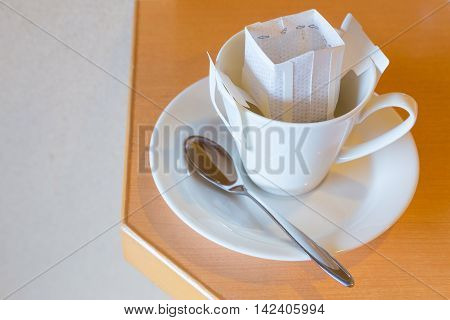 White coffee cup and spoon with white pre-packaged blended coffee in paper filter set