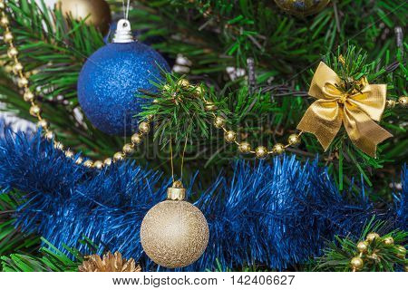 Christmas decorations on a green artificial fir. Golden and bright blue on a green background. Fragment. Photo with limited depth of field.