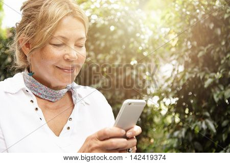 Portrait Of Good-looking Mature Woman With Fair Hair Using Smart Phone, Typing Messages Via Social N